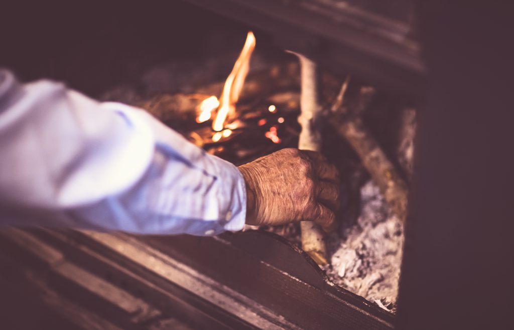 Man kindle a fire in the fireplace, grandpa making warmth and cozy atmosphere in the country house, romantic and peaceful winter evening